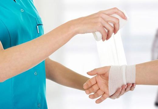врач делает перевязку руки